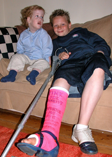 Mel's son Jack with Tom Lennox. Jack had his blue cast changed to pink to raise money for the Myotubular Trust.