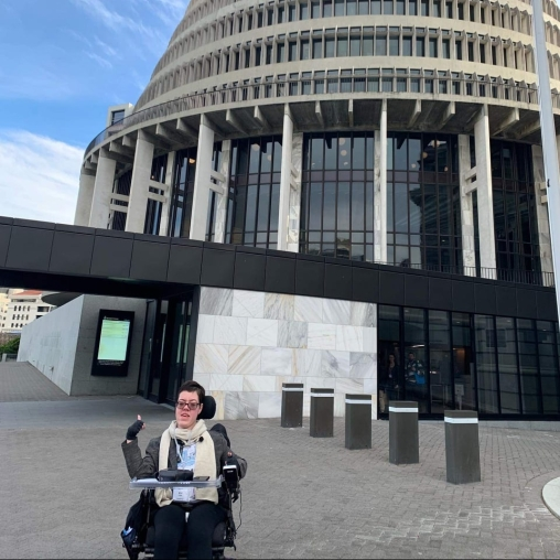 Kim outside the new Zealand parliament building.